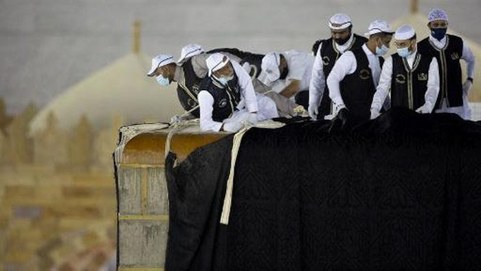 Saudi labourers put the new Kiswa, the protective cover that engulfs the Kaaba, made from black silk and gold thread and embroidered with Koran verses, on July 29, 2020 in Saudi Arabia's holy city of Mecca. - The drape which engulfs the Kaaba is formally called Kiswa and is changed every year at the culmination of the annual hajj, or pilgrimage, when the hajjis have left Mecca to go to Arafat, the starting point of their hajj journey. (Photo by - / AFP)