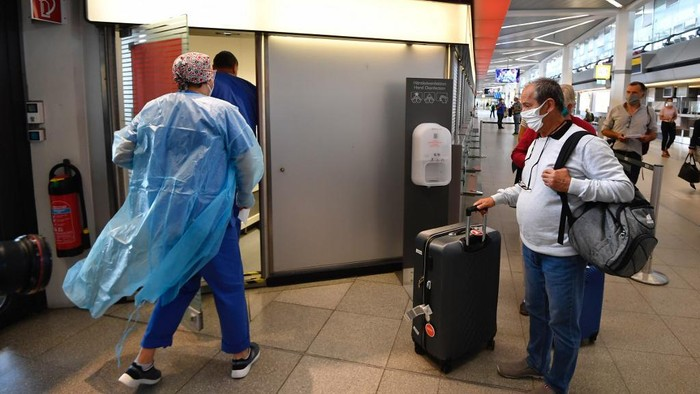 A passenger waits at a test station for the novel coronavirus that can cause the COVID-19 disease at terminal A of Berlin Tegel airport on July 29, 2020. - Germany made coronavirus tests mandatory for travellers returning from at-risk areas, as fears grow over rising case numbers blamed on summer holidays and local outbreaks. (Photo by Tobias SCHWARZ / AFP)