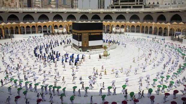 In this photo released by the Saudi Media Ministry, limited numbers of pilgrims, move several feet apart, circling the cube-shaped Kaaba in the first rituals of the hajj, as they keep social distancing to help prevent the spread of the coronavirus, in the Muslim holy city of Mecca, Saudi Arabia, Wednesday, July 29, 2020. The hajj, which started on Wednesday, is intended to bring about greater humility and unity among Muslims. (Saudi Media Ministry via AP)