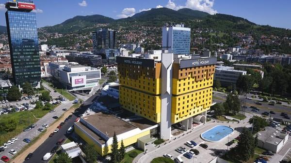 Holiday Inn di Sarajevo pertama kali membuka pintunya saat Olimpiade Musim Dingin tahun 1984. Bangunan kuning cerah yang terletak di pusat Sarajevo ini sering dibandingkan dengan balok-balok Lego dan dirancang oleh arsitek terkenal Bosnia, Ivan Straus. AP Photo/Kemal Softic