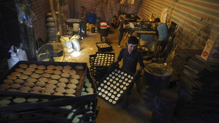 Vendors prepare sweets at a traditional bakery for the upcoming Muslim festival Eid al-Adha in Kabul, Afghanistan, Thursday, July 30, 2020. Eid al-Adha, or
