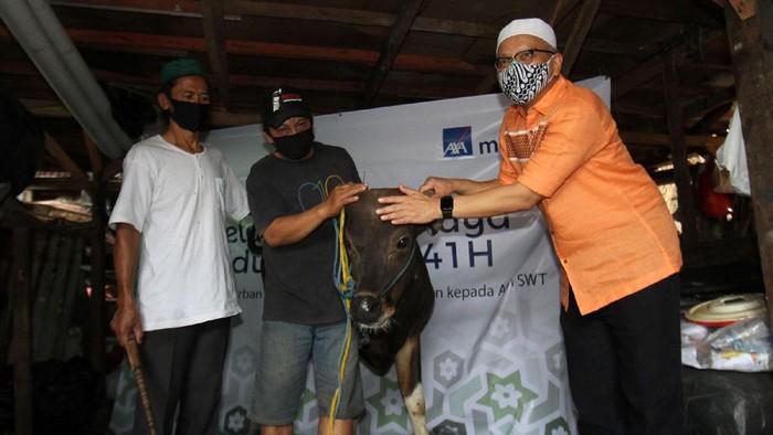 Direktur Kepatuhan PT AXA Mandiri Financial Services (AXA Mandiri) Rudy Kamdani (kanan) menyerahkan hewan kurban kepada perwakilan warga Kampung Pemulung Pelangi, Ustad Gandhi (kiri), di wilayah Cipete Utara, Antasari, Jakarta Selatan, Jumat (31/7).
