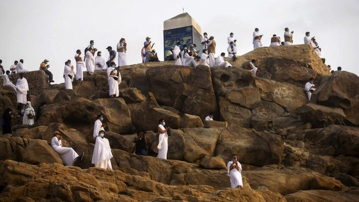 Muslim pilgrims pray on top of the rocky hill known as Mountain of Mercy on the Plain of Arafat during the annual hajj pilgrimage near the holy city of Mecca, Saudi Arabia, Thursday, July 30, 2020. Only about 1,000 pilgrims will be allowed to perform the annual hajj pilgrimage this year due to the virus pandemic. (Saudi Ministry of Media via AP)