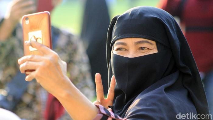 Sebagian jemaah Masjid Raya Bandung langsung menyerbu Taman Alun-alun Kota Bandung begitu khutbah hari raya selesai disampaikan, Jumat (31/7/2020). Warga terlihat antusias melakukan swafoto atau pun sekedar duduk santai.