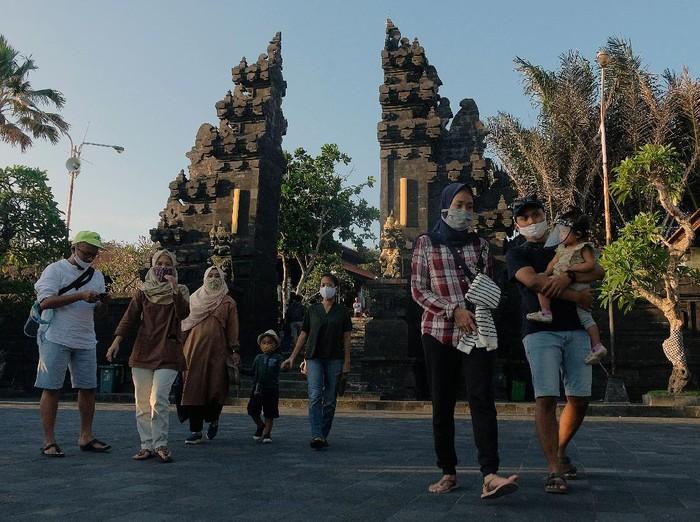Wisatawan domestik menggunakan masker saat liburan Idul Adha 1441H di masa Adaptasi Kebiasaan Baru tahap II di obyek wisata Tanah Lot, Tabanan, Bali, Sabtu (1/8/2020). Obyek wisata tersebut mulai dikunjungi wisatawan dari luar Pulau Bali dengan menerapkan protokol kesehatan COVID-19 meskipun jumlahnya masih sedikit. ANTARA FOTO/Nyoman Hendra Wibowo/nym/wsj.