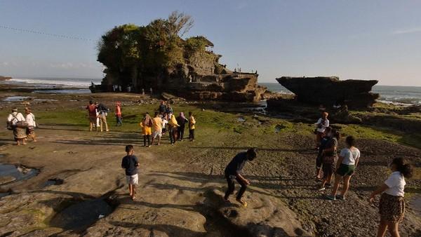 Wisatawan domestik menikmati pemandangan saat liburan Idul Adha 1441H di masa Adaptasi Kebiasaan Baru tahap II di obyek wisata Tanah Lot, Tabanan, Bali, Sabtu (1/8/2020).