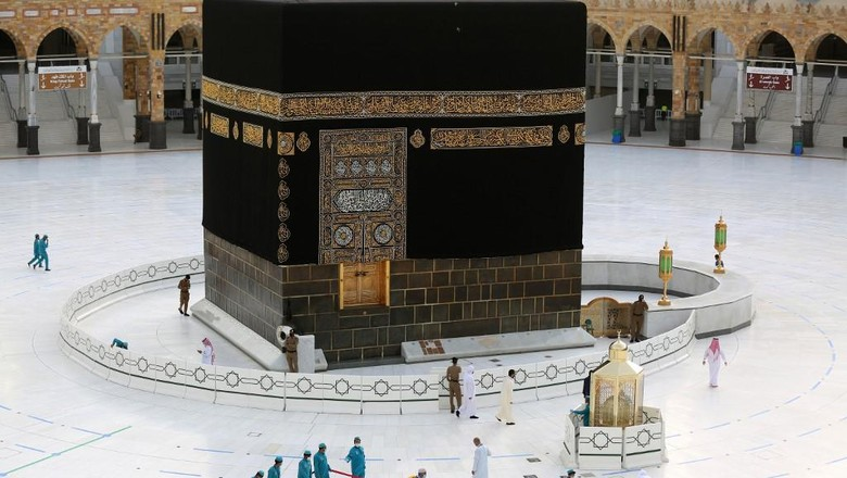 Workers clean and disinfect around the Kaaba on August 1, 2020, traced with lines for easing the physical distancing between pilgrims due to the coronavirus, during the evening before the last day of circumambulation around the shrine, in the Grand mosque of the holy Saudi city of Mecca, during the annual Muslim Hajj pilgrimage (Photo by - / AFP)