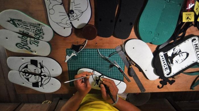Seorang perajin mengukir sandal jepit pesanan konsumen, di Nagari Kamang Hilia, Agam, Sumatera Barat, Minggu (2/8/2020). Selain mengukir sandal, perajin tersebut juga membuat berbagai suvenir seperti gantungan kunci dan pajangan dinding dengan bahan karet sandal yang dijual mulai Rp10 ribu hingga jutaan rupiah. ANTARA FOTO/Iggoy el Fitra/pras.