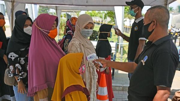 Sejumlah warga mengantre untuk diukur suhu tubuhnya dengan menggunakan thermal gun saat hendak berwisata ke makam Kesultanan Banten di Kasemen, Serang. Sejumlah protokol kesehatan wajib dipatuhi oleh para pengunjung tempat wisata guna mencegah penyebaran virus Corona.