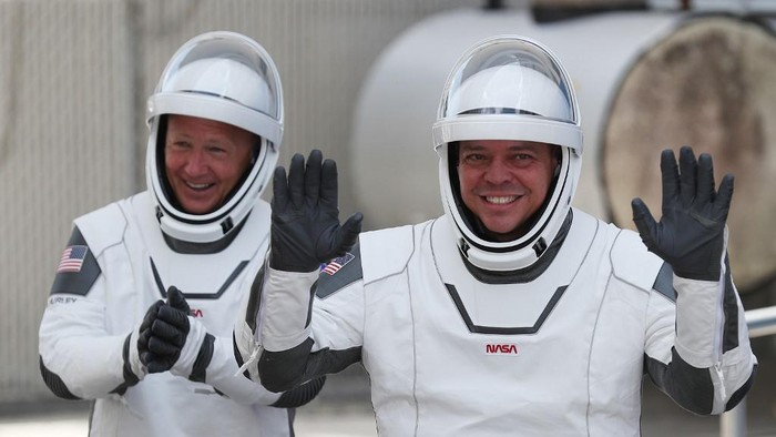 (FILES) In this file photo taken on May 30, 2020, NASA astronauts Bob Behnken (R) and Doug Hurley walk out of the Operations and Checkout Building on their way to the SpaceX Falcon 9 rocket with the Crew Dragon spacecraft on launch pad 39A at the Kennedy Space Center in Cape Canaveral, Florida. - The first US astronauts to reach the International Space Station on an American spacecraft in nearly a decade might not come home this weekend as scheduled because of Hurricane Isaias, NASA said July 31, 2020. (Photo by JOE RAEDLE / GETTY IMAGES NORTH AMERICA / AFP)