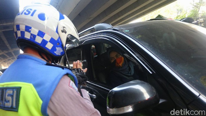 Petugas polisi sosialisasi secara langsung kepada pengemudi yang melanggar Ganjil Genap di Perempatan Rawamangun, Jalan Pramuka, Jakarta Timur, Senin (3/8/2020). Sistem ganjil kendaraan bermotor di 25 ruas jalan di DKI Jakarta kembali berlaku mulai hari ini, Senin (3/8).
