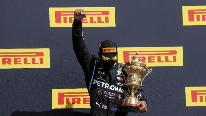 Mercedes driver Lewis Hamilton of Britain hold trophies after winning the British Formula One Grand Prix at the Silverstone racetrack, Silverstone, England, Sunday, Aug. 2, 2020. (Will Oliver/Poolvia AP)
