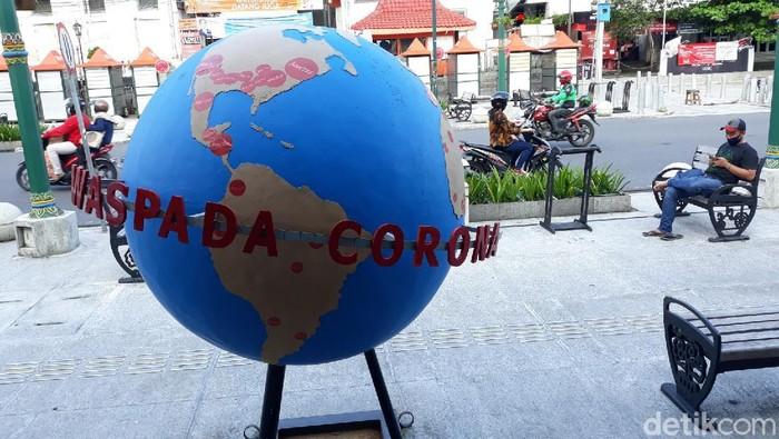 Properti peringatan waspada virus Corona atau COVID-19 di Titik Nol Kilometer Yogyakarta.