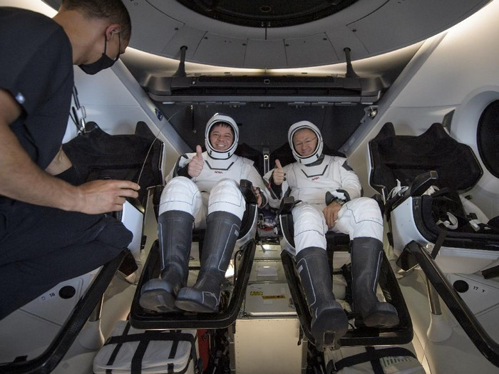 NASA astronauts Robert Behnken, left, and Douglas Hurley are seen inside the SpaceX Crew Dragon Endeavour spacecraft onboard the SpaceX GO Navigator recovery ship shortly after having landed in the Gulf of Mexico off the coast of Pensacola, Fla., Sunday, Aug. 2, 2020. The Demo-2 test flight for NASAs Commercial Crew Program was the first to deliver astronauts to the International Space Station and return them safely to Earth onboard a commercially built and operated spacecraft. Behnken and Hurley returned after spending 64 days in space. (Bill Ingalls/NASA via AP)