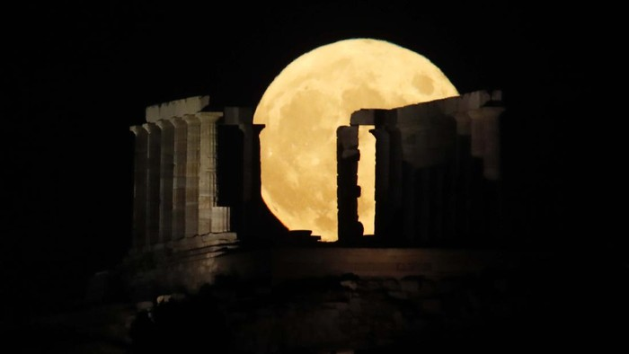 The moon rises over the columns of the ancient marble Temple of Poseidon at Cape Sounion, about 70 Km (45 miles) south of Athens, Monday, Aug. 3, 2020. (AP Photo/Thanassis Stavrakis)