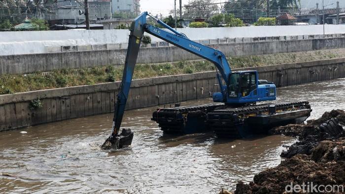 Petugas menggunakan alat berat melakukan proses pengerukan endapan tanah di aliran Sungai Ciliwung, Jakarta, Selasa (4/8/2020). Hal ini dilakukan guna mencegah sedimentasi dan ketika musim hujan daya tampung sungai bertambah.
