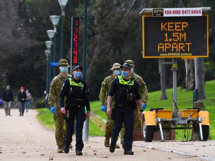 Police officers and soldiers patrol a popular running track in Melbourne on August 4, 2020 after the state announced new restrictions as the city battles fresh outbreaks of the COVID-19 coronavirus. - Australias Victoria state imposed fresh, sweeping restrictions on August 2, 2020, including a curfew in Melbourne for the next six weeks, a ban on weddings, and schools and universities going back online in the coming days. (Photo by William WEST / AFP)