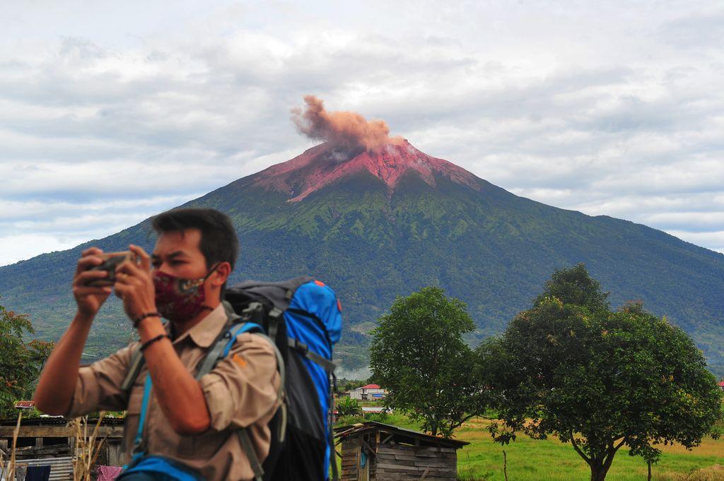 Warga mengamati suasana perkampungan saat Gunung Kerinci mengembuskan gas dan material yang terlihat dari Gunung Tujuh, Kerinci, Jambi, Rabu (5/8/2020). Pos Pengamatan Gunung Api Kerinci menyebutkan Gunung Kerinci yang statusnya masih berada pada level II (waspada) kembali mengalami gempa embusan dan tremor menerus yang terpantau secara visual dan data seismik pada Rabu (5/8) pagi. ANTARA FOTO/Wahdi Septiawan/aww.