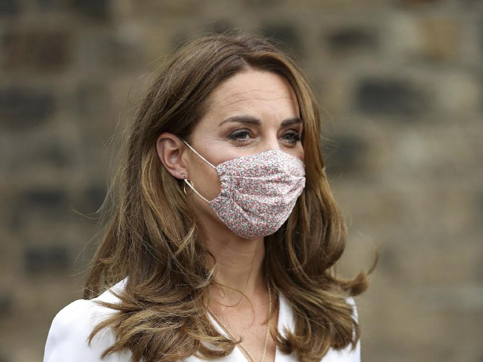 Britains Kate, the Duchess of Cambridge, wears a face mask to protect against coronavirus, as she talks to parents Ali Wartty and Sahara Hamawandy about their triplets San, Shan and Laveen, during a visit to Baby Basics Sheffield, in Sheffield, England, Tuesday, Aug. 4, 2020. Baby Basics is a volunteer led project which supports families in need struggling to provide for their newborns. (Chris Jackson/PA via AP)