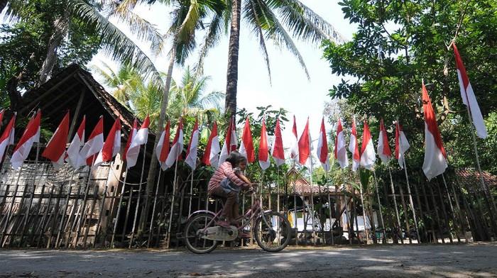 Warga melintas di dekat bendera merah putih terpasang di kediaman Asim di Bayat, Klaten, Jawa Tengah, Rabu (5/8/2020). Asim melanjutkan tradisi turun temurun yang telah dilakukan sejak tahun 1995 oleh keluarganya dengan memasang bendera merah putih sebanyak usia negara Indonesia di rumahnya untuk memperingati HUT Kemerdekaan Republik Indonesia dan tahun ini ia memasang sebanyak 75 bendera merah putih sebagai edukasi kepada generasi muda agar tetap mencintai NKRI. ANTARA FOTO/Aloysius Jarot Nugroho/foc.