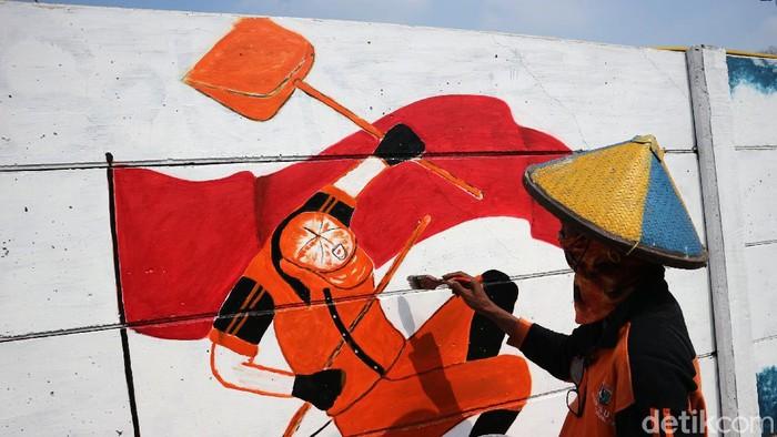 Petugas PPSU Kelurahan Cakung Timut menghiasi dinding dengan gambar di Jalan Pangeran Komarudin, Cakung, Jakarta Timur, Rabu (5/8/2020). Menjelang kemerdekaan Agustusan PPSU menghiasi dinding kota dengan gambar tema kemerdekaan guna memperindah kota.