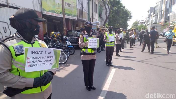 Pihak kepolisian Tanjung Perak terus mengimbau masyarakat agar menerapkan protokol kesehatan. Polisi membagikan masker bagi mereka yang tidak menggunakan.