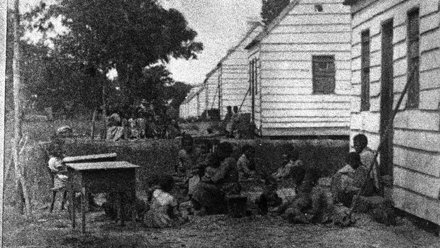 A group of slave children sit around behind the shacks in which they are forced to live on a plantation, South Carolina, 1860. (Photo by Hulton Archive/Getty Images)