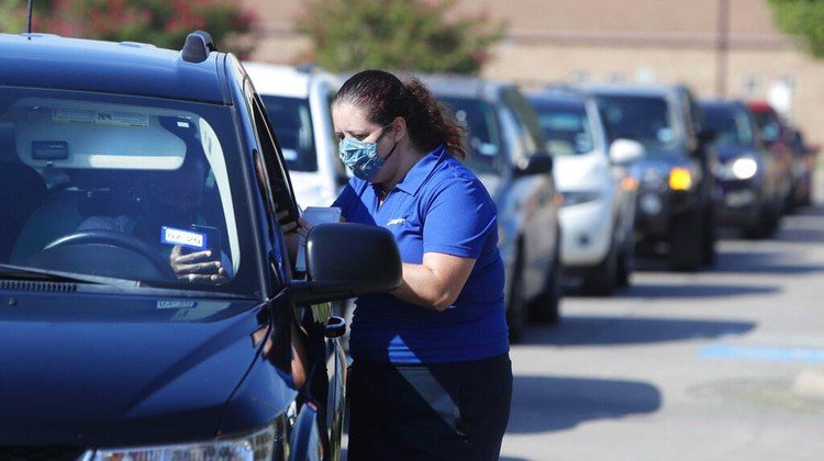 Wearing a mask to prevent the spread of COVID-19, Megan Steckly, CEO of Com-U-Dot, checks a driver in a line of cars as they wait to receive a computer during a drive through event in Dallas, Tuesday, Aug. 4, 2020. TXU Energy and Comp-U-Dopt partnered with the City of Dallas to give away 400 computers to middle school students to use when school starts. (AP Photo/LM Otero)