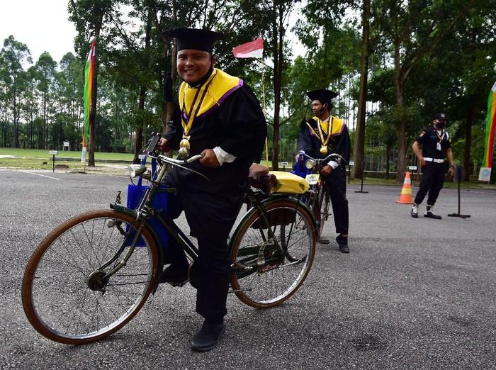 Universitas Lancang Kuning Riau gelar wisuda drive thru di tengah pandemi COVID-19. Sejumlah wisudawan pun hadiri wisuda drive thru dengan menaiki sepeda onthel