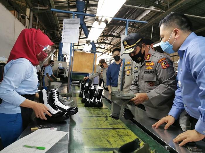 Anggota polisi melihat produksi sepatu dalam negerib