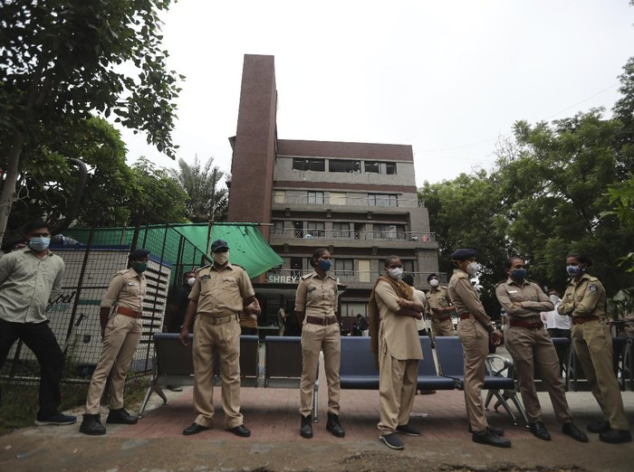 Police officers stand guard outside Shrey hospital, where a fire broke out early morning in Ahmedabad, India, Thursday, Aug. 6, 2020. Firefighters and 15 fire engines contained the fire to the intensive care unit at Shrey Hospital and it was extinguished in half an hour, fire officer Yusuf Khan said. (AP Photo/Ajit Solanki)