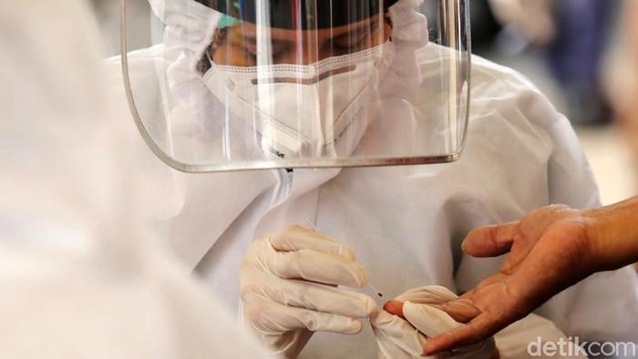 Petugas kesehatan menegambil sample darah warga yang mengikuti rapid test di Depan Kejaksaan Agung, Jakarta, Kamis (6/7/2020). Kejaksaan Agung menggelar tes cepat massal. Tes diikuti para pengendara ataupun pejalan kaki yang melintas kawasan tersebut dalam upaya pencegahan covid-19.
