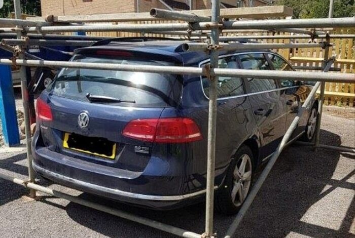 Sebuah Volkswagen Passat dikerangkeng pipa besi karena dianggap parkir sembarangan