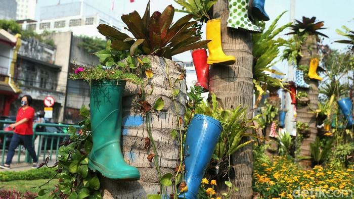 Selain terlihat asri, taman di kawasan Kota Tua, Jakarta, terlihat keren dan unik. Taman tersebut dilengkapi pot bunga yang terbuat dari sepatu boot.