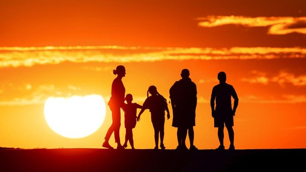 Orang-orang berdiri bersama saat matahari terbenam, di Halde Norddeutschland, Neukirchen-Vluyn, Jerman. Marcel Kusch/dpa via AP