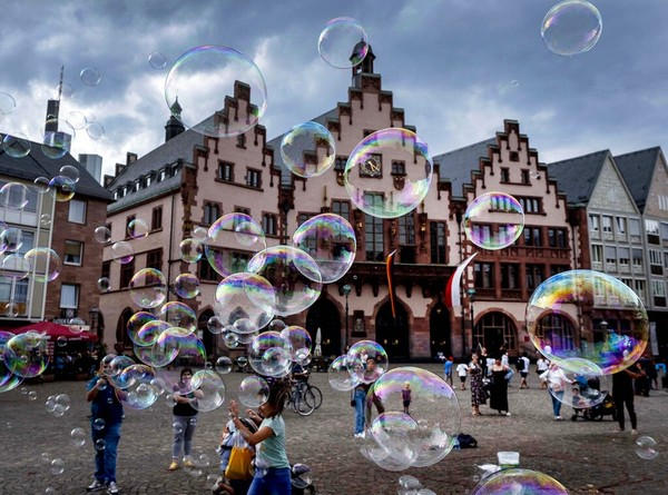 Seorang seniman jalanan membuat gelembung di depan balai kota di Frankfurt, Jerman. AP Photo/Michael Probst