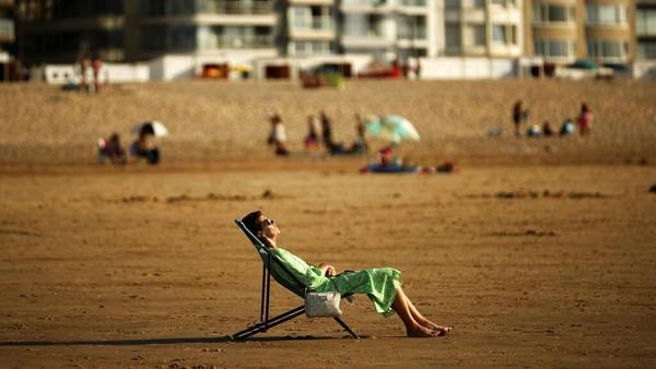 Seorang wanita berjemur saat musim panas di pantai Zoute di Knokke-Heist, Belgia utara. AP Photo/Francisco Seco