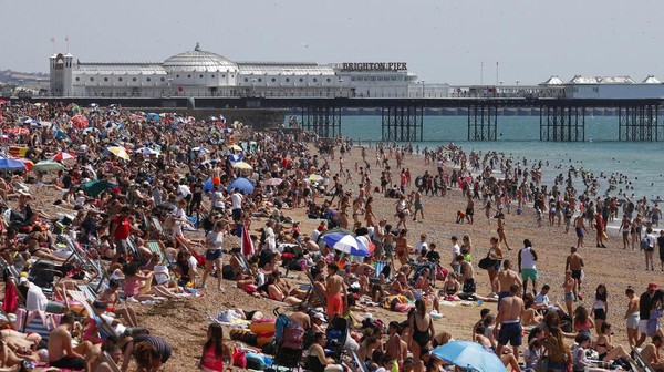 Para pengunjung pantai menikmati sinar matahari dan laut saat hari terpanas di Inggris. AP Photo/Alastair Grant
