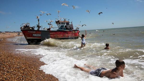 Anak-anak bermain di laut saat kapal nelayan kembali dari laut di Hastings, Inggris. Dan Kitwood/Getty Images