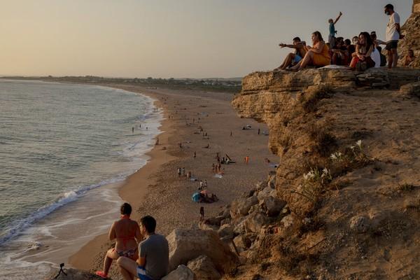 Orang-orang menyaksikan matahari terbenam dengan duduk di tebing di samping Mercusuar Trafalgar di Los Caños de Meca, kota Barbate di provinsi Cadiz, Spanyol. AP Photo/Emilio Morenatti