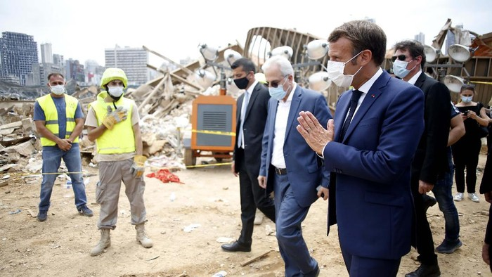 French President Emmanuel Macron, center, visits the devastated site of the explosion at the port of Beirut, Lebanon, Thursday Aug.6, 2020. French President Emmanuel Macron has arrived in Beirut to offer French support to Lebanon after the deadly port blast.(AP Photo/Thibault Camus, Pool)