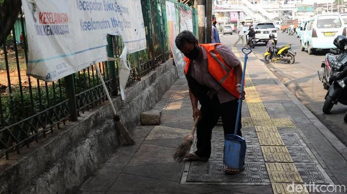 Satpol PP melakukan razia masker di Kampung Melayu, Jakarta, Jumat (7/8). Warga yang kedapatan tidak memakai masker dihukum dengan membersihkan trotoar.