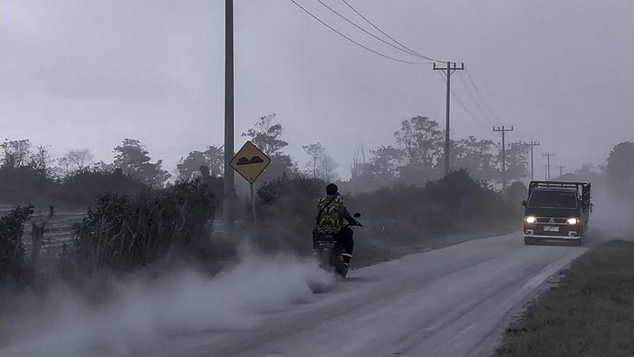 Warga membersihkan jalan yang dipenuhi debu vulkanik pasca erupsi Gunung Sinabung, di Desa Sigarang-garang, Karo, Sumatera Utara, Sabtu (8/8/2020). Gunung Sinabung erupsi dengan tinggi kolom 2.000 meter. ANTARA FOTO/Sastrawan Ginting/Lmo/hp.
