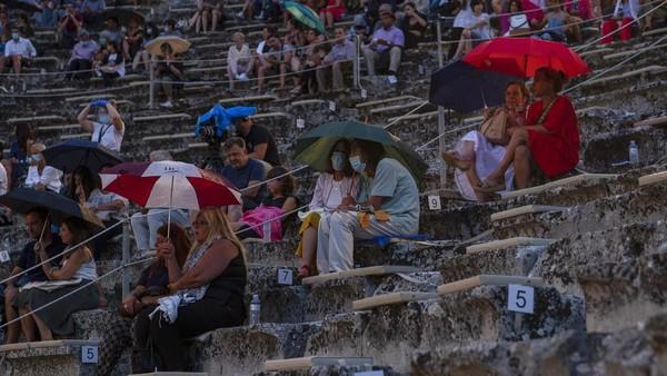 Penonton memegang payung saat hujan turun sebelum drama di teater mulai.