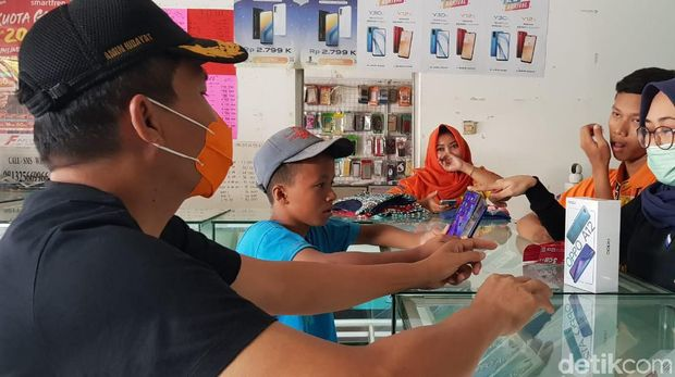 Catur Ferianto (16) pelajar yang jadi kuli tampak sibuk memilih smartphone, Sabtu (8/8/2020)