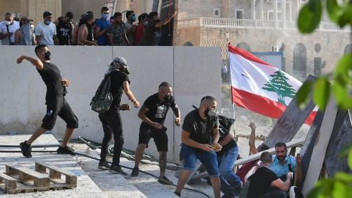 Lebanese protesters duck for cover during clashes with security forces in downtown Beirut on August 8, 2020, following a demonstration against a political leadership they blame for a monster explosion that killed more than 150 people and disfigured the capital Beirut. (Photo by - / AFP)