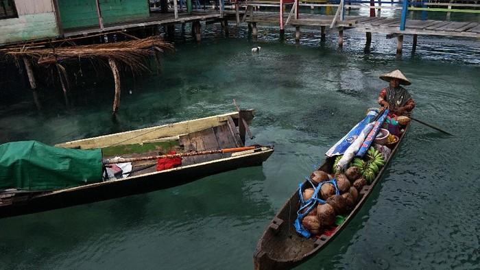 Nadi Riakurabi (kanan) menjajakan dagangannya dari atas perahu di perkampungan di atas laut suku Bajo, Torosiaje, Kabupaten Pohuwato, Gorontalo, Minggu (9/8/2020). Pedagang perahu keliling yang menjual bumbu dapur, sayuran dan bahan pangan lainnya tersebut menjadi salah satu alternatif warga untuk memenuhi kebutuhan harian selain ke pasar yang berada di daratan. ANTARA FOTO/Adiwinata Solihin/foc.