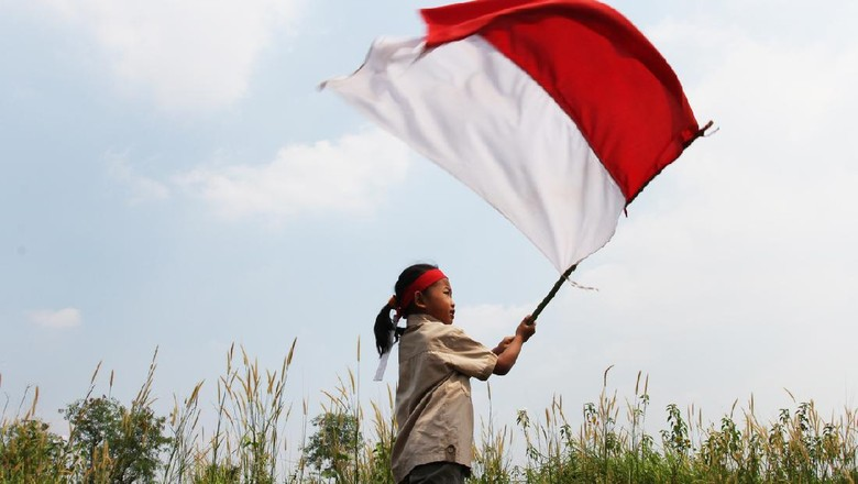 Beautiful young mother with her daughter celebrating indonesia independence day by raising flag under the sunset sky