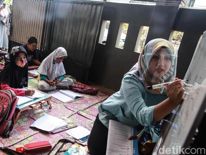 Murid kelas IV SD Muhammadiyah 37 belajar pada teras rumah seorang guru di kawasan Pondok Cabe Udik, Tangerang Selatan, Banten, Senin (10/8/2020). Kegiatan belajar mengajar (KBM) tatap muka dengan menerapkan standar protokol kesehatan ini terpaksa dilakukan karena murid kesulitan menguasai materi pelajaran saat proses belajar secara online.