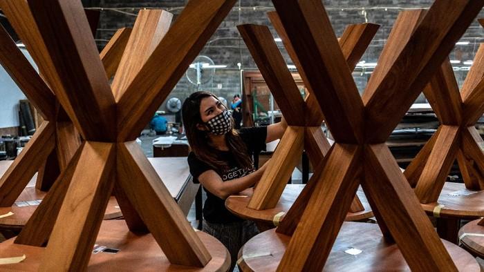 Sejumlah pekerja dengan mengenakan masker dan menjaga jarak menyelesaikan pesanan furnitur kualitas ekspor di perusahan furnitur PT Saniharto Enggalhardjo di Demak, Jawa Tengah.